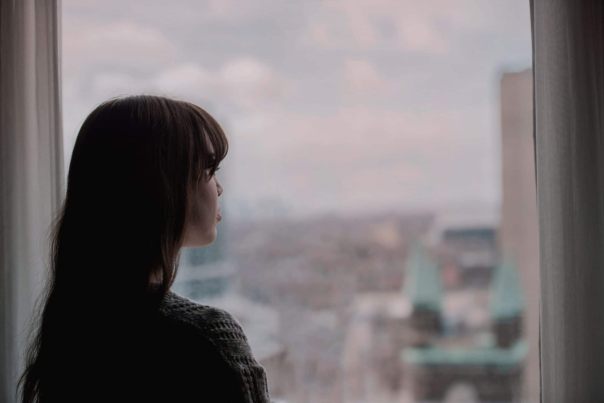 Woman staring out a window at a city.