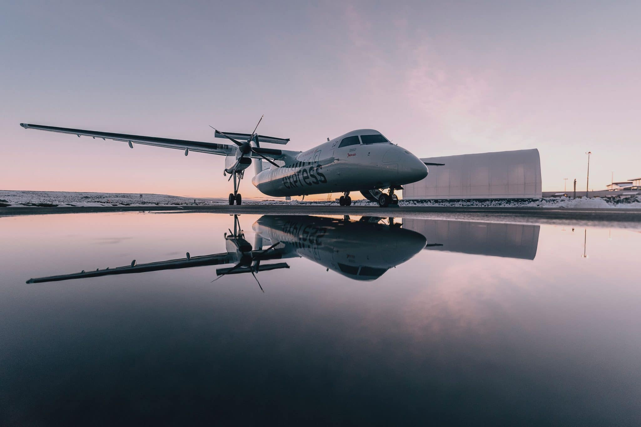 Jet sits on wet runway at dusk casting a perfect reflection.