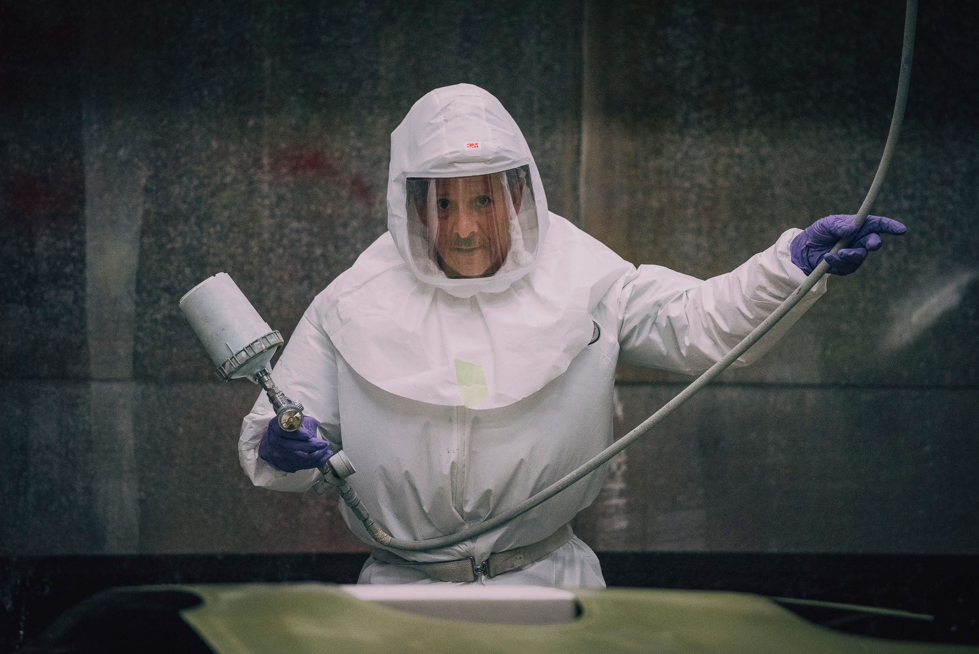 Man in hazmat suit holds a maintenance tool.