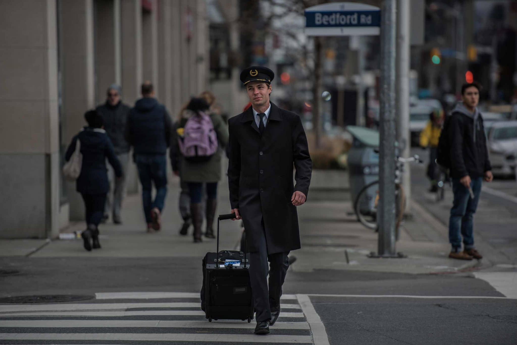 Pilot in uniform crosses the street with luggage.