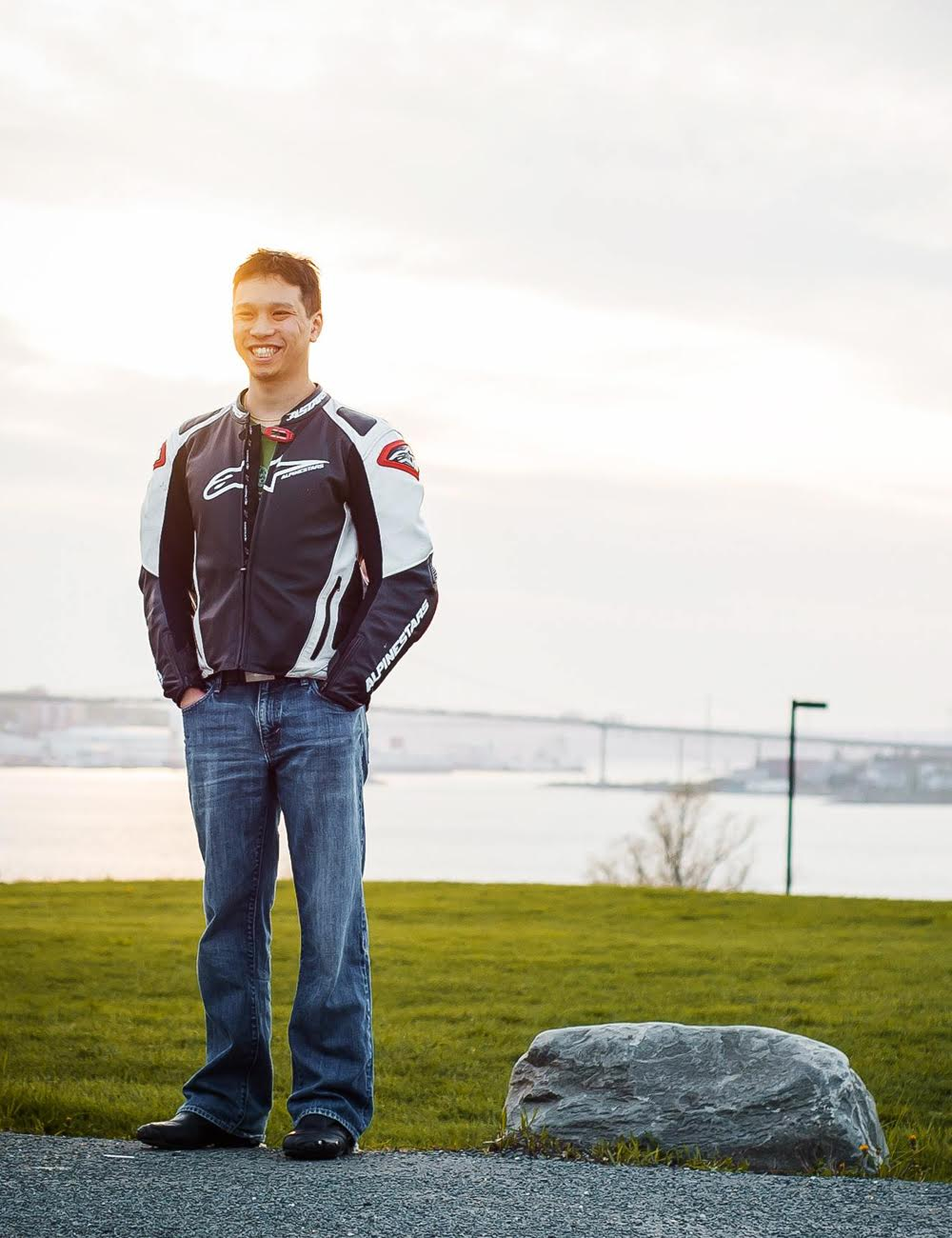 Man stands next to rock and grass in racing jacket.