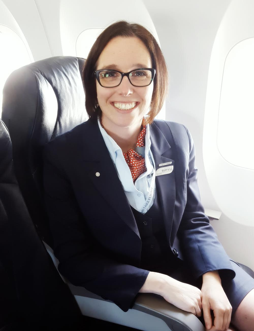 Flight attendant seated on aircraft.