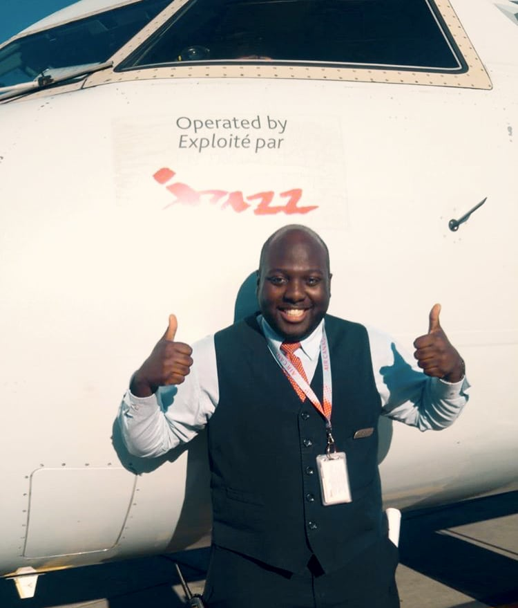 Airline employee thumbs up in front of Jazz aircraft.