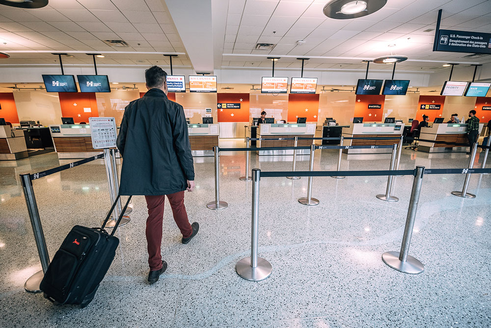 Passenger approaching airport check-in desk with luggage.