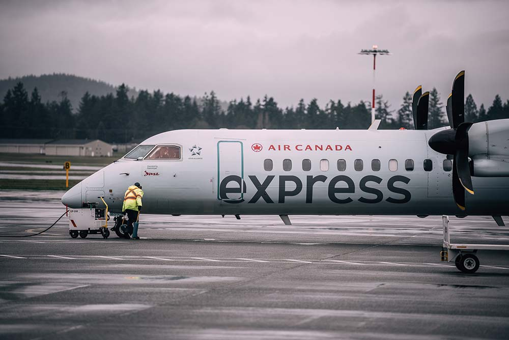 Ground service next to Air Canada express plane.