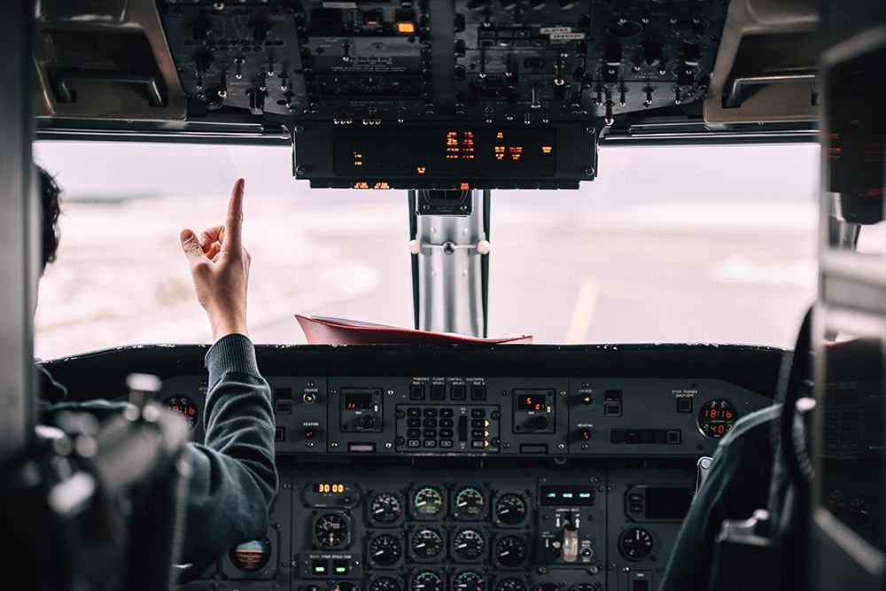 Pilot pointing out cockpit window on runway.
